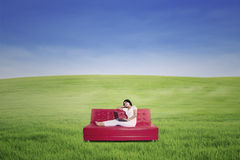 Woman using laptop on sofa at meadow Stock Images