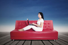 Woman using laptop on sofa outdoors Stock Photo