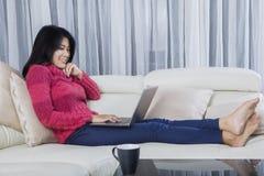 Woman using laptop on sofa Royalty Free Stock Image