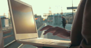 Woman using laptop at the station platform. Close-up shot of a woman typing on laptop at the railway station at sunset. She leaving after finishing the work stock footage