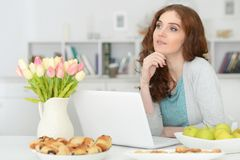 Woman  using  laptop  at table Royalty Free Stock Images