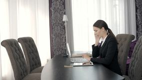 Woman using laptop at the table in office, young freelancer in modern presidential suite working stock footage