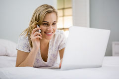 Woman using laptop while talking on mobile phone in bed Stock Photos
