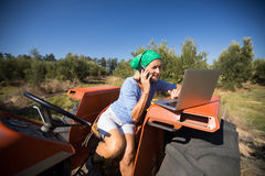 Woman using laptop while talking on mobile phone. In olive farm Royalty Free Stock Images