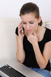 Woman using a laptop and talking on phone. Pensative young woman using a laptop and talking on phone at home royalty free stock images
