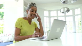Woman Using Laptop And Talking On Phone In Kitchen At Home stock footage
