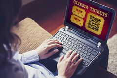 Woman using a laptop to buy cinema tickets online in a website. Stock Photography