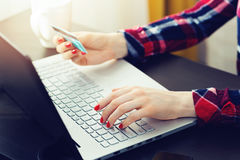 Woman using laptop to make online payment with credit card. At home Stock Photo
