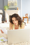 Woman Using Laptop To Manage Laying On Rug Royalty Free Stock Photos