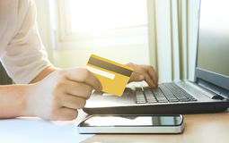 Woman using laptop to online shopping and paying credit card. Stock Photos