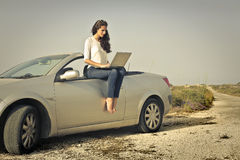 Woman using laptop on top of the car Royalty Free Stock Photo