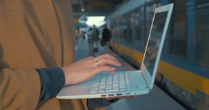 Woman using laptop by train at the station stock footage