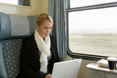 Woman using laptop traveling by train commuter. Serious technology reading Royalty Free Stock Photo