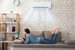 Woman Using Laptop Under The Air Conditioner. Woman Lying On Sofa Using Laptop Enjoying The Cooling Of Air Conditioner At Home royalty free stock photo