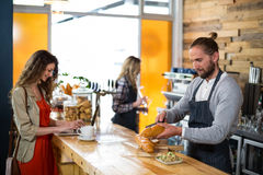 Woman using laptop and waiter cutting bread at counter Stock Photo