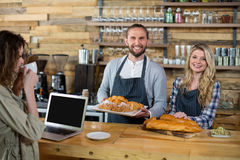 Woman using laptop and waiter and waitress working at counter Royalty Free Stock Image