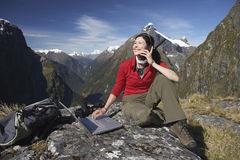 Woman Using Laptop And Walkie Talkie Against Mountains stock images