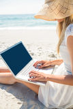 Woman using laptop and wearing hat Royalty Free Stock Photography
