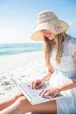 Woman using laptop and wearing hat Stock Images