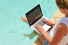 Woman Using Laptop Whilst Dangling Feet In Swimming Pool Royalty Free Stock Photo