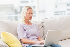 Woman using laptop white sitting on sofa. In living room stock images