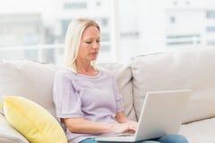 Woman using laptop white sitting on sofa Stock Images