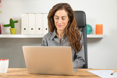 Woman using laptop in workplace Royalty Free Stock Image