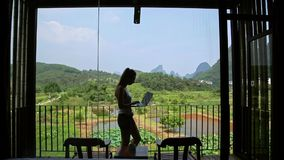 Woman Using Laptop. Young woman surfing on internet outside the house on the terrace with a view over Guiling mountain landscape in Yangshuo County,China stock footage