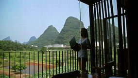 Woman Using Laptop. Young woman surfing on internet outside the house on the terrace with a view over Guiling mountain landscape in Yangshuo County,China stock video footage