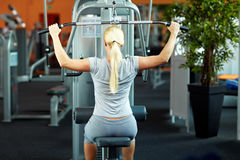 Woman using lat machine. Woman doing exercises on a lat machine in a gym royalty free stock photography
