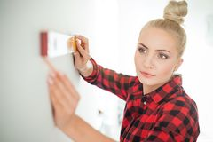 Woman using leveling tool at home royalty free stock photography