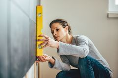 Woman using leveling tool Royalty Free Stock Photos