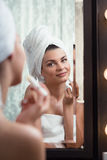 Woman using lip balm Stock Image