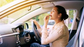 Woman using lipstick inside car. Urban background. Bad busy royalty free stock images