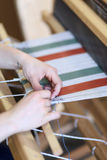 Woman using loom. Woman using a foot-treadle floor loom with threads Royalty Free Stock Photography