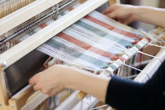 Woman using loom. Woman using a foot-treadle floor loom with threads Stock Image