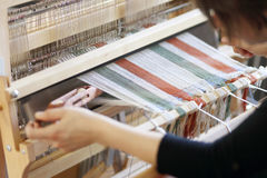 Woman using loom. Woman using a foot-treadle floor loom with threads Stock Photos