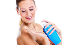 Woman using lotion Stock Images