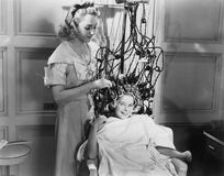 Woman using machine to style teenage girls hair. (All persons depicted are no longer living and no estate exists. Supplier grants that there will be no model Stock Photography