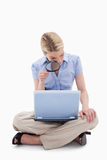 Woman using magnifier to look at her laptop Royalty Free Stock Photography