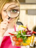 Woman investigating shopping backet with vegetables royalty free stock photography
