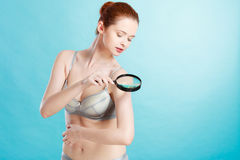 Woman using magnifying glass to examine her moles skin. Skin control self examination concept. Yound woman holds magnifying glass in hand examining her body for Stock Images