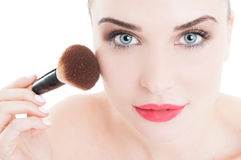 Woman using make-up brush on face cheeks Stock Photo