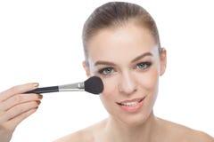 Woman using make-up brush, isolated on white background. Smiling woman using make-up brush, doing her make-up or some touch ups. Isolated on white stock photo