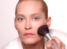 Woman using makeup brush Stock Images