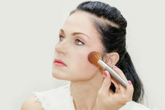 Woman using makeup brush for blush Royalty Free Stock Image