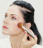 Woman using makeup brush Stock Photo