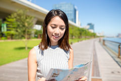 Woman using map to find the location Stock Image