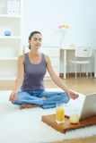 Woman using meditating at home Stock Images