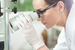 Woman using microscope in laboratory. Woman using microscope in a laboratory, horizontal Royalty Free Stock Photos